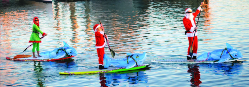 Standup paddleboarders show off their decorative human-powered vessels during the King Harbor Boat Parade.
