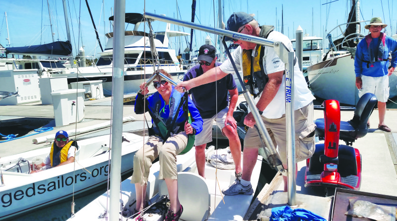 Challenged Sailors volunteers Bob Dillon, left, and Doug Shaw use the dockside hoist to assist participant Sue Taetzsch to board her boat as her sailing companion Joe Halsted stands by on the dock.  Capt. Nicole Sours Larson