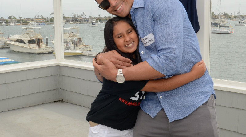 NFL great Tony Gonzalez, and El Viento Foundation ambassador, hugs a student at the El Viento Friend-Raiser held at Balboa Yacht Club.Photo courtesy of El Viento Foundation