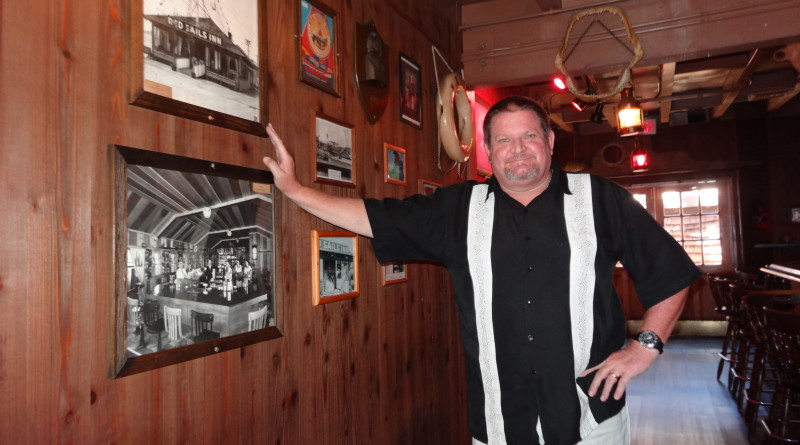 Current Red Sails Inn owner Bill Dargitz poses with early photos of the Red Sails Inn at its original location on the Embarcadero at G Street, where it operated in the 1920s and '30s. The restaurant will close its doors on Aug. 31 after a nearly 60-year run at its Shelter Island location. New owners The Brigantine Inc., which operates two other restaurants nearby, will remodel the restaurant and reopen it as The Ketch.Capt. Nicole Sours Larson photo